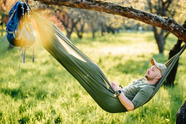 Glücklicher mann, der in der hängematte, die an apfelbaum im sonnigen sommerpark hängt, entspannt.