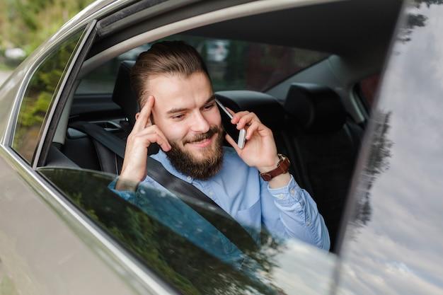 Glücklicher mann, der innerhalb des autos spricht auf smartphone sitzt