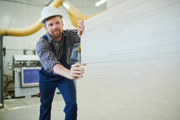 Glücklicher mann, der manuelle arbeit in der fabrik genießt