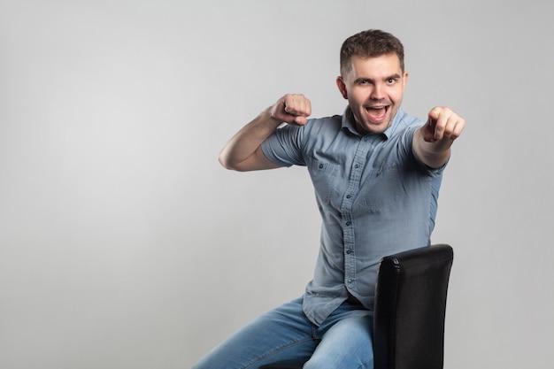 Glücklicher mann, der mit dem finger auf die kamera lächelt und zeigt. schauspieler portfolio bild, emotionen und gefühle. studioaufnahme, auf grauem hintergrund isoliert