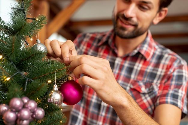 Glücklicher mann der nahaufnahme, der den weihnachtsbaum verziert