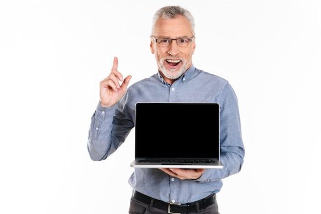 Glücklicher mann, der oben auf kopienraum zeigt, während laptop mit leerem bildschirm hält