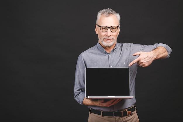 Glücklicher mann, der oben auf kopienraum zeigt, während laptop mit leerem bildschirm hält.