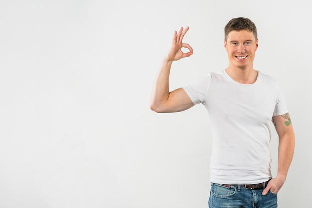 Glücklicher mann, der okayzeichen gegen weißen hintergrund zeigt