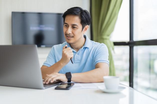 Glücklicher mann, der online mit laptop-computer zu hause am schreibtisch sitzt