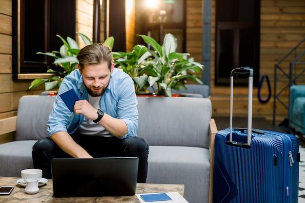 Glücklicher mann, der pass hält und laptop für buchung des zimmers und der karten vor langer reise verwendet