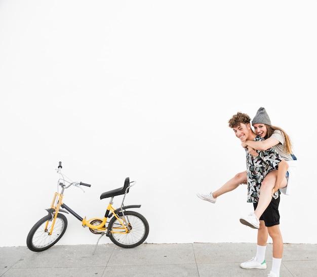 Glücklicher mann, der piggyback seinem nahe gelegenen gelben fahrrad der freundin gibt