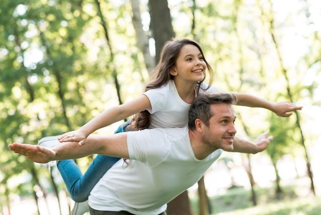 Glücklicher mann, der piggyback seiner schönen tochter mit den armen ausgestreckt im park gibt
