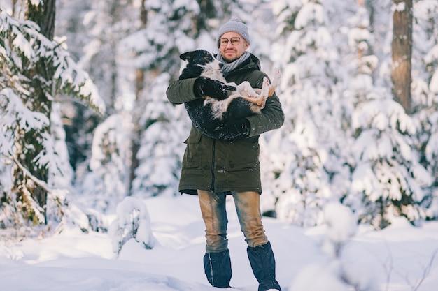 Glücklicher mann, der reizenden hund in seinen händen im schneebedeckten wald hält. lächelnder junge, der entzückenden welpen im winterholz umarmt. haustier liebhaber. hund - menschliches `s freundkonzept.