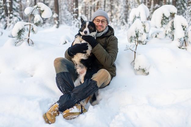 Glücklicher mann, der reizenden hund in seinen händen im schneebedeckten wald hält. lächelnder junge, der entzückenden welpen im winterholz umarmt.