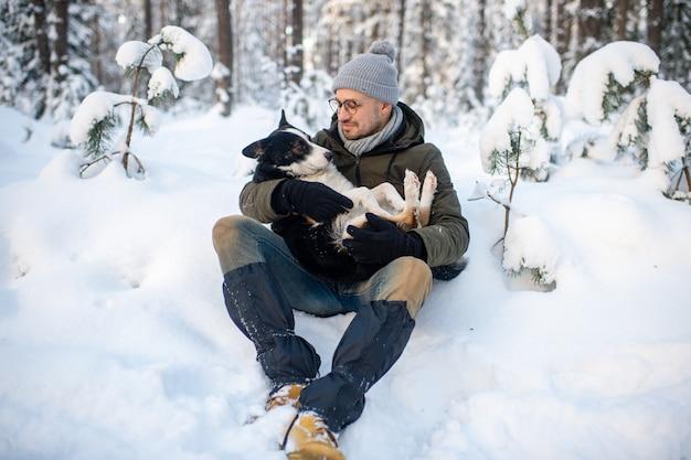 Glücklicher mann, der reizenden hund in seinen händen im verschneiten wald hält.