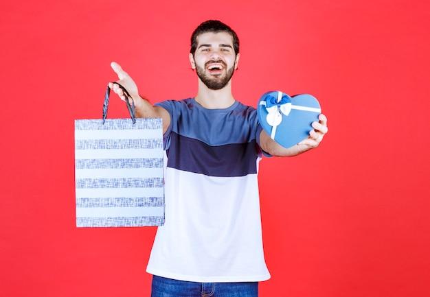 Glücklicher mann, der seine einkaufstasche und geschenkbox hält holding