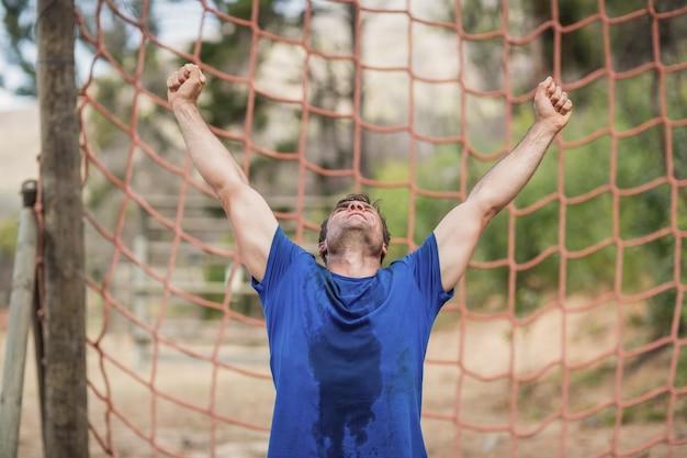 Glücklicher mann, der seine hände während des hindernislaufs im bootcamp erhebt