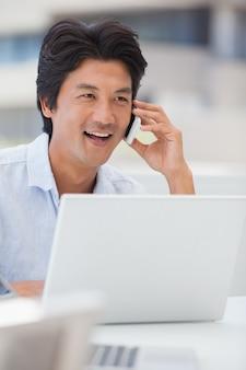 Glücklicher mann, der seinen laptop spricht am telefon verwendet