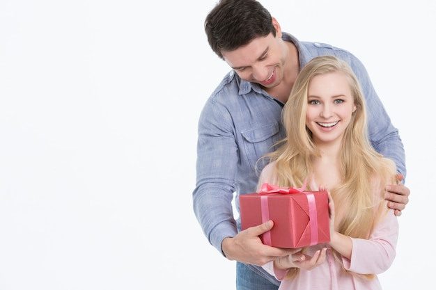 Glücklicher mann, der seiner freundin ein geschenk gibt. urlaub