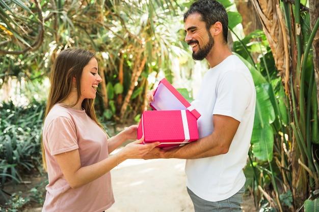 Glücklicher mann, der seiner freundin geschenk im park zeigt
