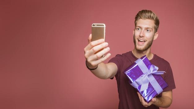 Glücklicher mann, der selfie mit dem mobiltelefon hält geschenkbox gegen farbigen hintergrund nimmt