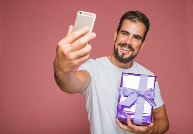 Glücklicher mann, der selfie mit dem mobiltelefon hält geschenkbox nimmt