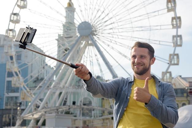 Glücklicher mann, der selfie vor riesenrad nimmt und daumen herauf geste zeigt