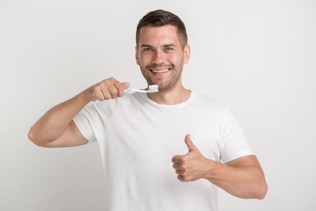Glücklicher mann, der sich daumen zeigt und zahnbürste mit paste hält