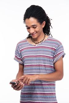 Glücklicher mann, der smartphone lokalisiert auf einer weißen wand verwendet