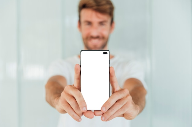 Glücklicher mann, der smartphone mit modell zeigt
