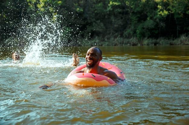 Glücklicher mann, der spaß beim lachen und schwimmen im fluss hat. freudige männliche modelle mit gummiring als donut am flussufer an sonnigem tag. sommerzeit, freundschaft, resort, wochenendkonzept.