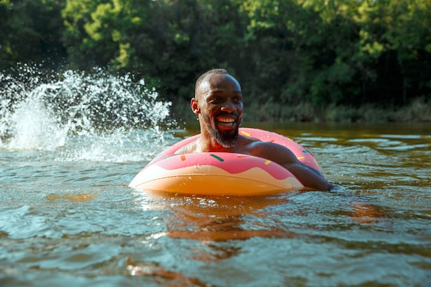 Glücklicher mann, der spaß hat, lacht und im fluss schwimmt