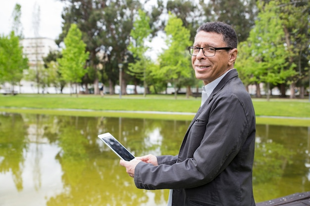 Glücklicher mann, der tablette verwendet und im stadtpark steht