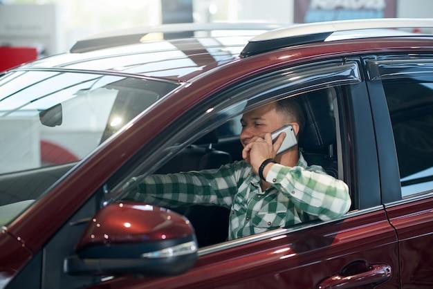 Glücklicher mann, der telefon im auto im autohaus benutzt.