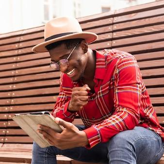 Glücklicher mann, der von seinem digitalen tablett liest