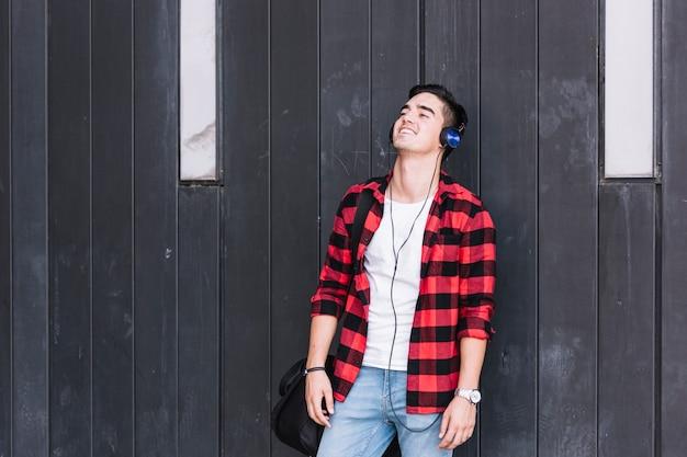 Glücklicher mann, der vor der hölzernen wand hört musik steht