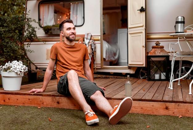 Glücklicher mann, der vor wohnmobil sitzt