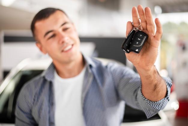 Glücklicher mann der vorderansicht, der autoschlüssel hält
