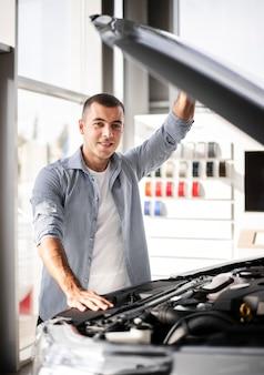 Glücklicher mann der vorderansicht, der ein auto überprüft