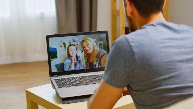 Glücklicher mann, der während der coronavirus-quarantäne mit seiner familie per videoanruf winkt.