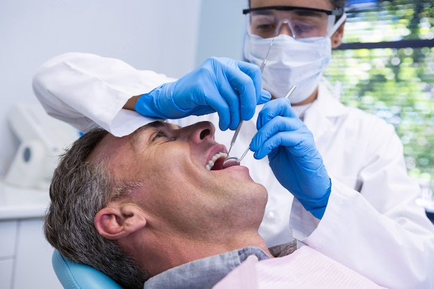 Glücklicher mann, der zahnbehandlung durch zahnarzt erhält