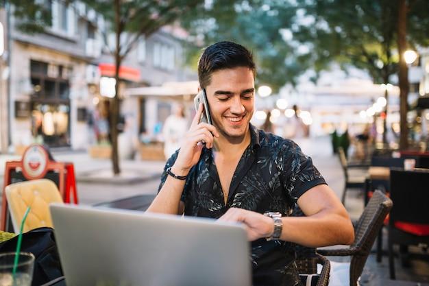 Glücklicher mann, der zeit auf armbanduhr bei der unterhaltung auf mobiltelefon betrachtet