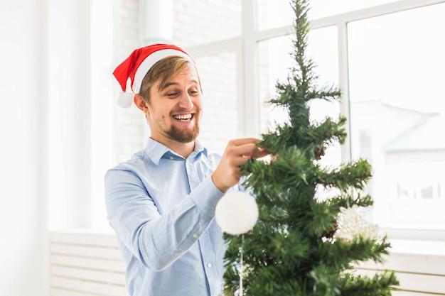 Glücklicher mann, der zu hause weihnachtsbaum mit weihnachtsmann-hut schmückt. mann, der während der winterferien baum mit kugeln schmückt.