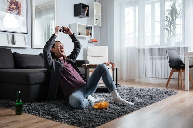 Glücklicher mann, der zuhause drinnen sitzt, spielt mit joystick