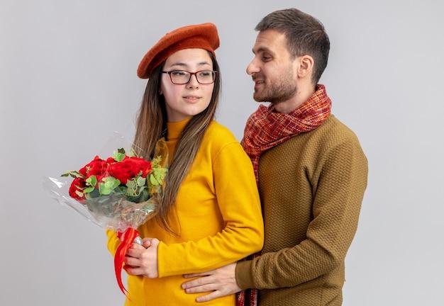 Glücklicher mann des jungen schönen paares, das seine lächelnde frau mit dem strauß der roten rosen umarmt, die in der liebe glücklich zusammen feiern und valentinstag feiern, der über weißer wand steht