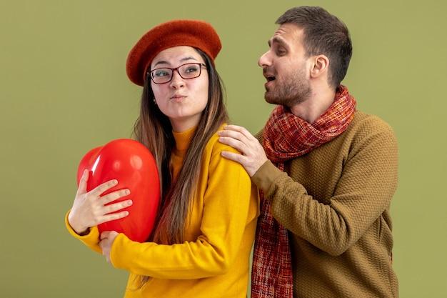 Glücklicher mann des jungen schönen paares, das seine verwirrte freundin in baskenmütze mit herzförmigem ballon berührt, der valentinstag feiert, der über grüner wand steht