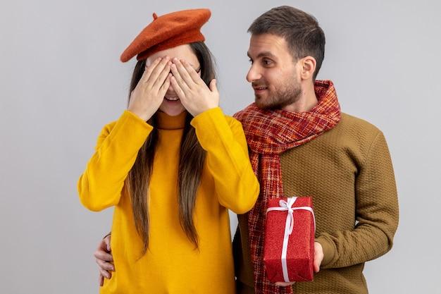 Glücklicher mann des jungen schönen paares, der ein geschenk für seine lächelnde freundin in der baskenmütze gibt, die augen mit den händen bedeckt, die in der liebe glücklich zusammen feiern, valentinstag feiern, der über weißem hintergrund steht