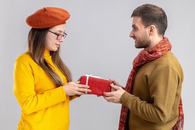 Glücklicher mann des jungen schönen paares, der ein geschenk für seine lächelnde freundin in der baskenmütze gibt, die in der liebe glücklich zusammen feiert und valentinstag feiert, der über weißer wand steht Kostenlose Fotos