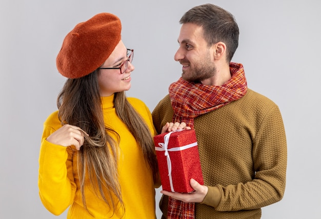 Glücklicher mann des jungen schönen paares, der ein geschenk für seine lächelnde freundin in der baskenmütze gibt, die in der liebe glücklich zusammen feiert und valentinstag feiert, der über weißer wand steht