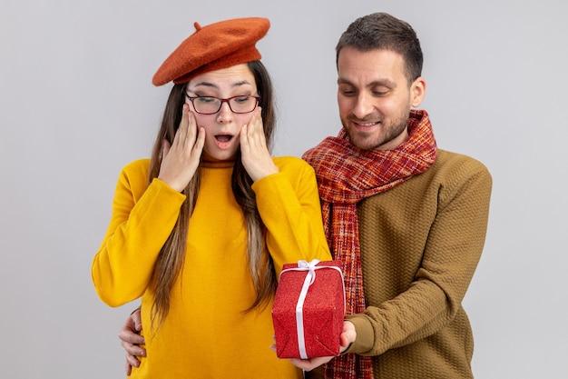 Glücklicher mann des jungen schönen paares, der ein geschenk für seine überraschte und glückliche freundin in der baskenmütze gibt, die in der liebe glücklich zusammen feiert und valentinstag feiert, der über weißer wand steht