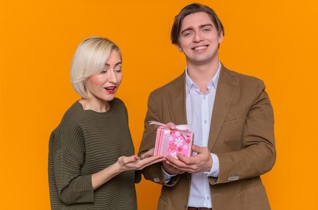 Glücklicher mann des jungen schönen paares, der seiner schönen lächelnden freundin, die glücklich in der liebe glücklich ist, ein geschenk gibt, das den internationalen frauentag feiert, der über orange wand steht