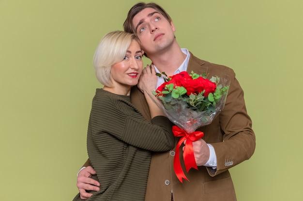 Glücklicher mann des jungen schönen paares mit blumenstrauß der roten rosen und der frau, die glücklich in der liebe zusammen umarmt, die valentinstag feiert