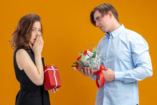 Glücklicher mann des jungen schönen paares mit dem strauß der roten rosen, die seine überraschte freundin mit geschenk betrachten, das valentinstag feiert, der über orange hintergrund steht