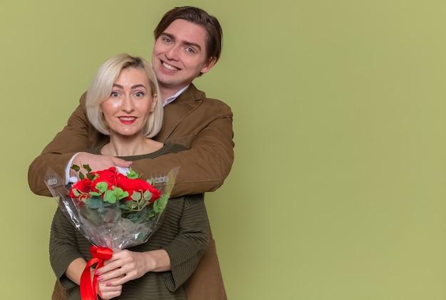 Glücklicher mann des jungen schönen paares mit dem strauß der roten rosen und der frau, die glücklich in der liebe zusammen umarmen, die den internationalen frauentag steht, der über grüner wand steht